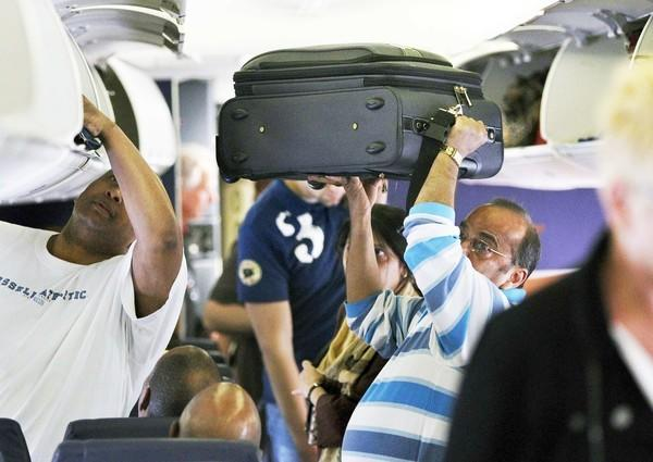Passengers load carry-on bags into overhead compartments.