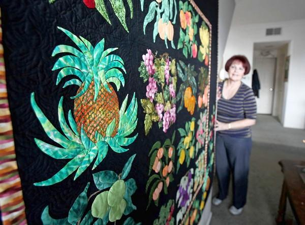Karen Powel stands proudly next to a wall-sized quilt on which she stitched various kinds of fruit. Powel is a finalist in a national quilt contest.