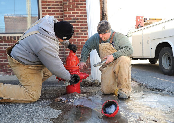 Winchester Municipal Utilities employees Jason Gomez, left, and Jeremiah Epperson check out a leaking fire hydrant Tuesday at the corner of East Broadway and Church Alley, top photo. Water from the leaking hydrant had quickly frozen, leaving a sheet of ice on the sidewalk and street corner. Water was slowly running out of the hydrant when workers arrived, right photo. Workers were trying to determine if the hydrant was damaged by the cold.