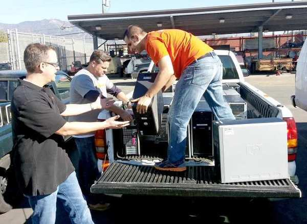 Nickelodeon employees, from left, Jack Kinman, Carson Smith and Alex Shandi, unload computers that were donated to the Burbank Unified School District Arts For All program.