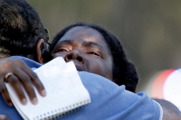 Lone Star College freshman Sheketa Taylor hugs her father Judson Gimblin after they found each other on the Lone Star Campus following Tuesday's shooting.