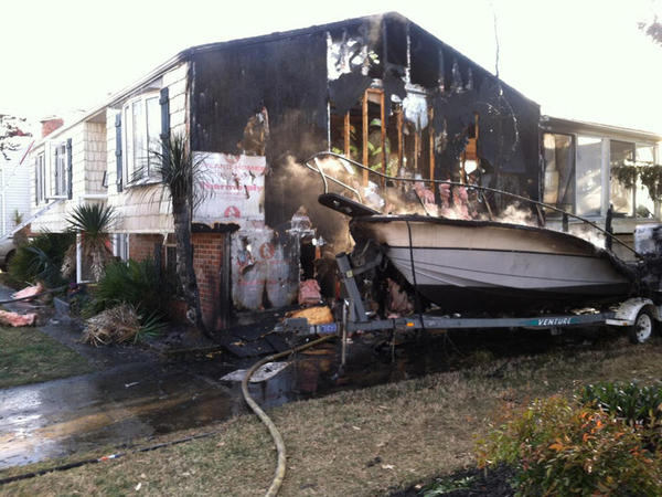 Firefighters check for hotspots after a fire that started in a parked boat spread to an adjoining home in Joppatowne Wednesday afternoon, damaging both extensively.