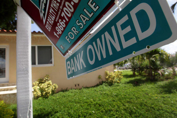 "A ""bank owned"" sign hangs in front of a foreclosed home in Miami."