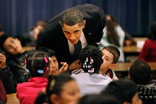 Decades of federal education reforms have resulted in a massive reshaping of the American education system. Above: President Obama asks third and fourth graders what they are reading during their lunch period at Viers Mill Elementary School in Silver Spring, Md.