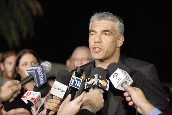 Yair Lapid speaks to journalists outside his house in Tel Aviv after his party's unexpectedly strong showing in Israeli parliamentary elections.