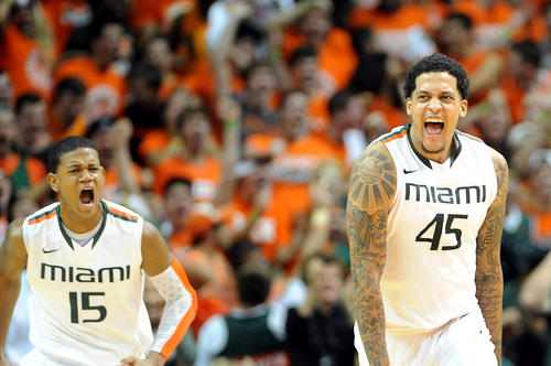 Miami's Julian Gamble at center and Rion Brown at left celebrate late in the fourth quarter as Duke's Alex Murphy walks by at right.