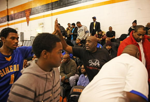 Simeon coach Robert Smith, center, high-fives Jaylon Tate after a victory Wednesday against Bogan.