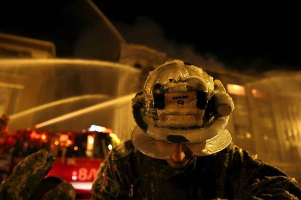 A Chicago firefighter is covered in ice while fighting the Bridgeport warehouse fire Tuesday night.