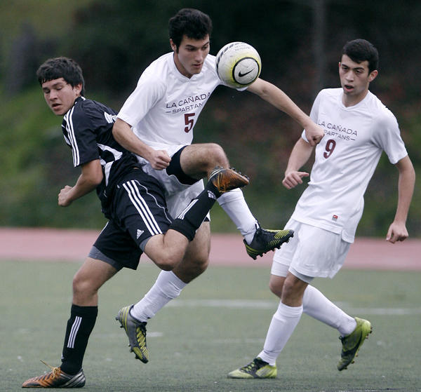 La Canada High School's #5 Shant Hairapetian battles for the ball vs. South Pasadena High School's #17 Daniel Zurita during home game in La Canada on Wednesday, January 23, 2013.  LCHS #9 is Armaan Zare.