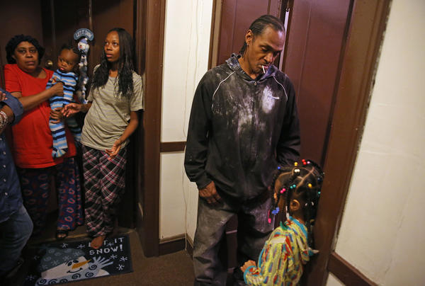 Resident Clyde Harden, who said he helped rescue the youngest of the three children hurt in an apartment fire, stands with fellow 4-flat residents after their apartment caught fire in the 1000 block of West 76th Street on Chicago's South Side.