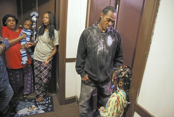 Clyde Harden, who said he helped rescue the youngest of the three children hurt in an apartment fire, stands with fellow neighbors Wednesday night after the blaze in the 1000 block of West 76th Street.