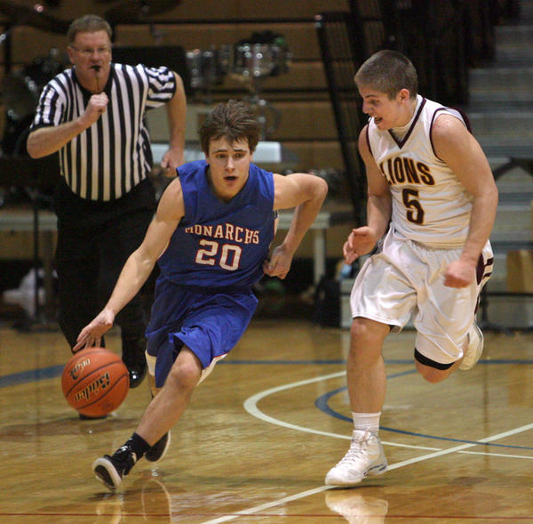 Warners Mitch Boesl, center, drives up the floor as Langford Areas Weston Hoglund, right, defends during a game at the Aberdeen Civic Arena last season. Boesl and the Monarchs return to the Civic Arena to face Aberdeen Roncalli at about 8 p.m. Saturday in the American News' Games of the Week.