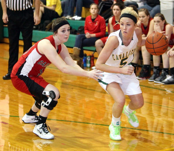 Aberdeen Roncalli¿s Morgan Gunderson, right, tries to get around Deuel¿s Haley Donahue, left, during a game at Roncalli Gym last week. Roncalli squares off against Warner at 6:30 p.m. Saturday at the Aberdeen Civic Arena.