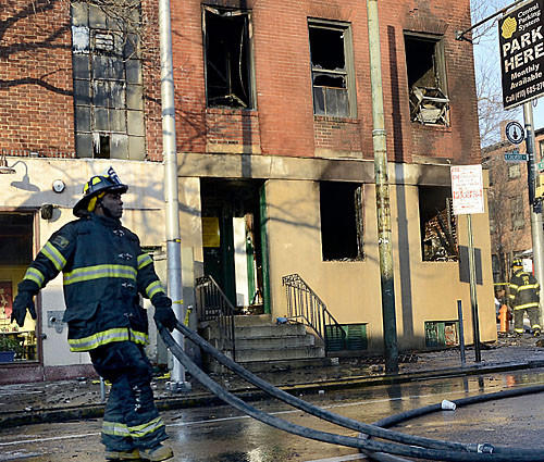 A firefighter gathers hose lines as they wrap up at the scene of an early morning three-alarm fire. The blaze gutted a three-story brick building at the corner of North Calvert and East Read Streets early Thursday morning, according to the Baltimore Fire Department.