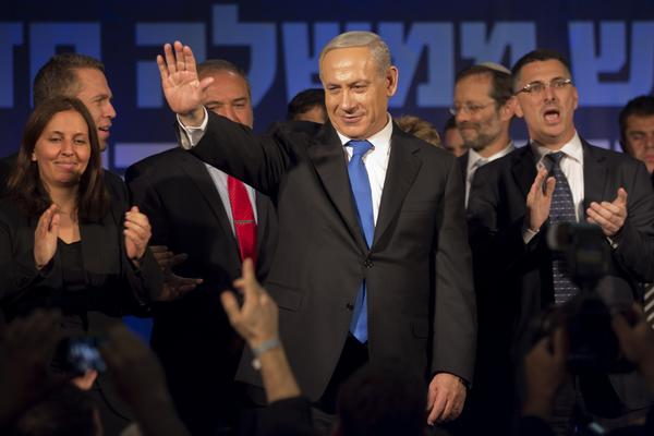 Israeli Prime Minister and chairman of the Likud party Benjamin Netanyahu, center, waves to supporters in the Tel Aviv party headquarters early Wednesday after his Likud-Beiteinu list came out on top in the Israeli general election.