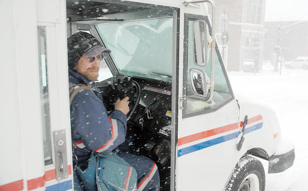 U.S. Postal delivery man Brian Florenski, hops into his mail van after walking part of his route in downtown Petoskey Wednesday. Florenski has been delivering mail at various routes in the Petoskey city limits for the past 19 years and didn't let Wednesday's snow and cold get in the way of his deliveries.