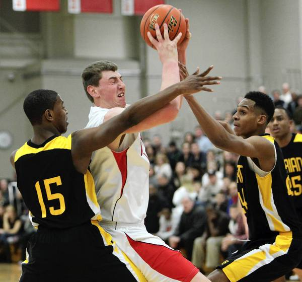Benet's Sean O'Mara goes for the basket as Marian Catholic's John Oliver, left, and Terrone Parham tries to block at Benet High School.