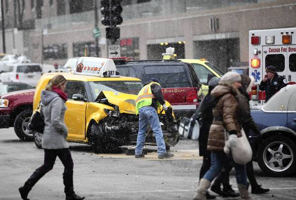 Chicago police and Chicago firefighters work at the scene of an accident with Truck Co. 6 and a taxi at the intersection of Michigan Avenue and Wacker Drive in Chicago.The firetruck was being driven to a fire when the collision occurred.