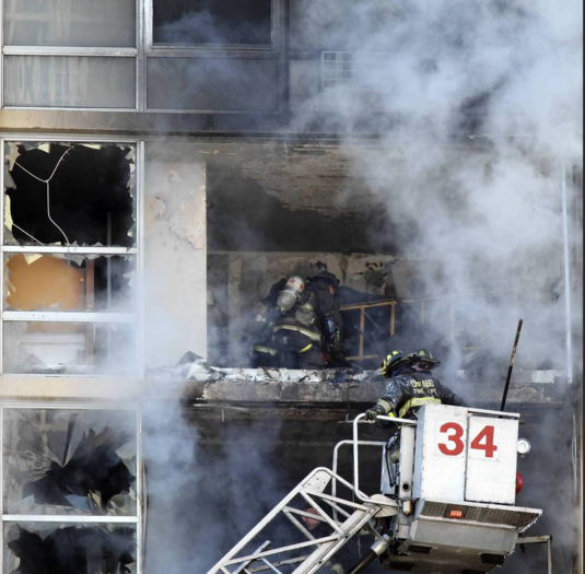 Firefighters work to extinguish a fire on the seventh and eighth floors of a high-rise apartment building at 6730 South Shore Drive in Chicago