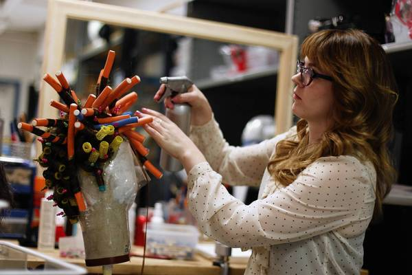 "Brittany Crinson, associate wig maker and makeup artist, curls hair Monday, Jan.14, 2013 on a wig to be worn in ""La Boheme"" by singer Elizabeth Futral, who plays Musetta in the Lyric Opera of Chicago presentation at the Civic Opera House."