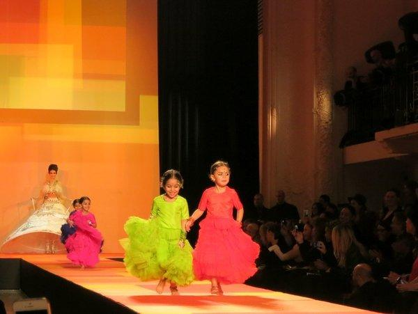 Four colorfully clad children race along Jean Paul Gaultier's runway on Wednesday before a model clad as a bride.