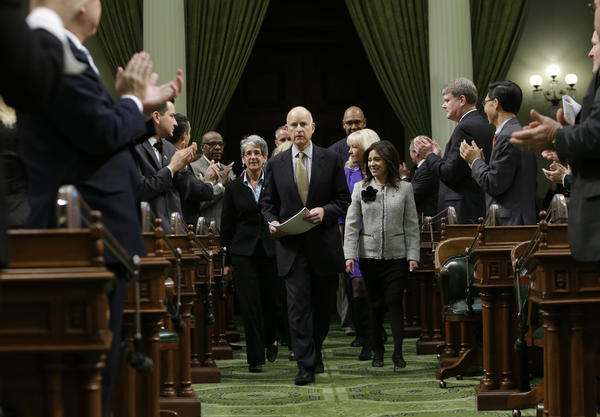 Lawmakers applaud Gov. Jerry Brown as he enters the Assembly chamber to give his State of the State address.