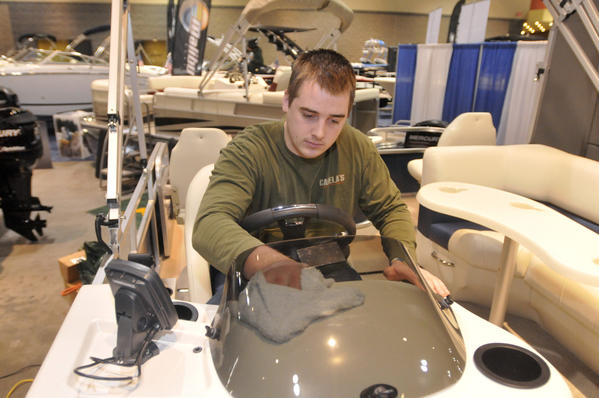 Kyle Foley, a Cabela employee, wipes down the dashboard of a Lowe pontoon boat at the Connecticut Marine Trades Association's Hartford Boat Show Thursday. The boat show runs through Sunday at the Connecticut Convention Center.