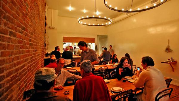 The small, ambitious restaurant is like a rolling dinner party for the neighborhood. Long tables, small plates, natural wines and no reservations.