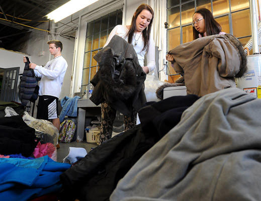 Kevyn McConlogue (left) and Diane Park (right) both members of the Emmaus High School Key Club along with other volunteers from the Business and Community Alliance, and the Emmaus Kiwanis Club, sort through and count an estimated 2200 coats that were collected in the Lehigh Valley to help the victims of super storm Sandy Thursday afternoon. Once the coats have been sorted, they will be given to Hills Cleaners and Village West Dry Cleaners to be cleaned. The coats will be delivered to distribution centers in New York and New Jersey to assist the victims of the super storm.