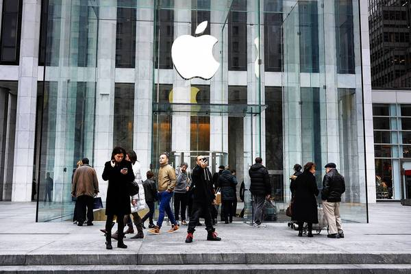 People walk in front of the flagship Apple store on Fifth Avenue in New York City. A sell-off of Apple stock is underway as investors realize that the tech giant may not continue posting stratospheric growth numbers.