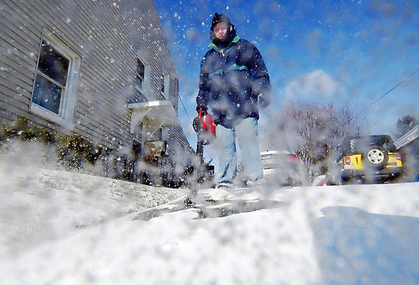 Bob Myers uses a leaf blower to clear snow from his driveway Thursday on Stratford Avenue in Hagerstown.