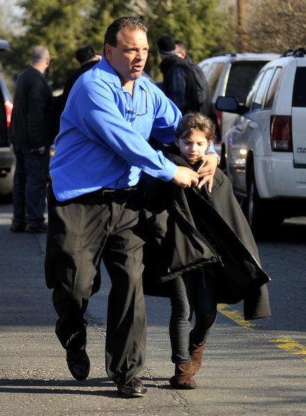 A father wraps his jacket around his daughter after leaving the scene at Sandy Hook Elementary School Friday morning.