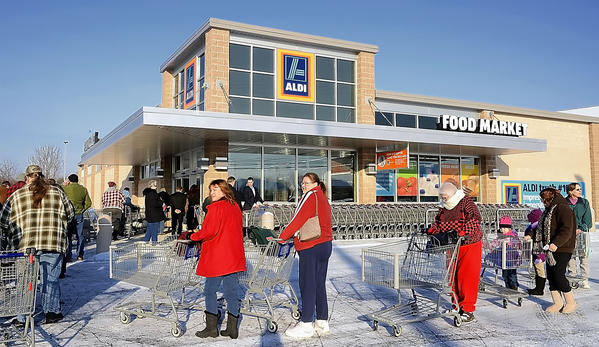 Customers wait outside the ALDI grocery store in Martinsburg, W.Va., Thursday for the store's opening.