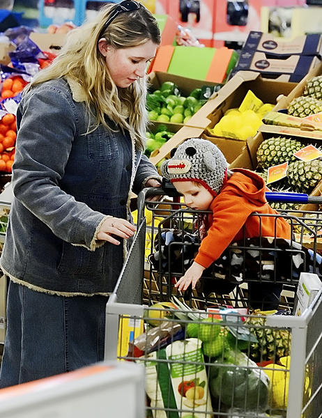 Garrison Thorn reaches for a food item with his mother, Mandy Thorn, at the new ALDI's store in Martisnburg, W.Va., Thursday.