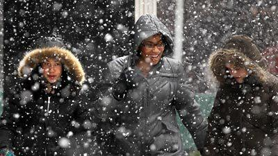People walk through swirling snow on Michigan Avenue in downtown Chicago Thursday.