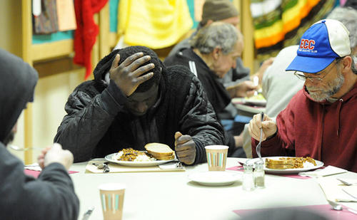 Sedale Isaac of Bethlehem, (left) prays prior to eating his dinner at the Cathedral Church of the Nativity in Bethlehem as the church opens it's doors to homeless men Thursday night. The men stay the night at the church's Sayre Hall as part of a revolving shelter at local churches during the winter months.