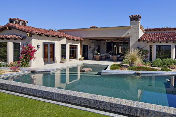 A swimming pool with a spa hugs the back of the house.