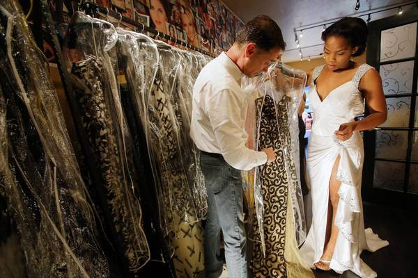 Carry O'Neal, co-owner of Regalia, helps Louissa Nevy, who will be competing in the Citrus Pageant.
