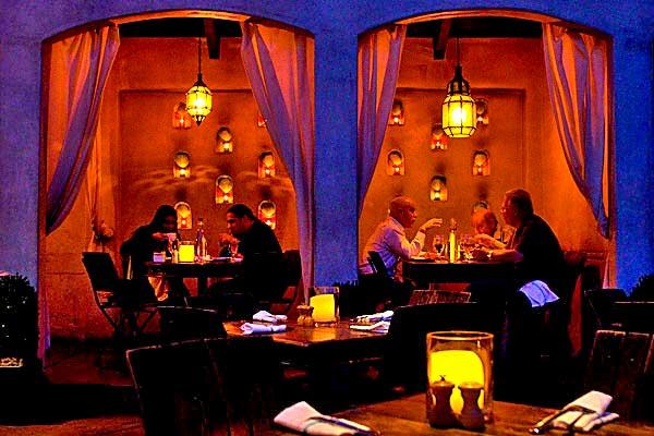 The atmospheric dining area at Firefly features two fireplaces and curtained cabanas.