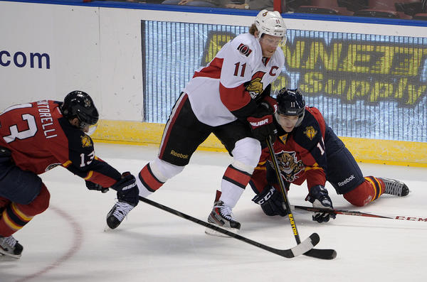Florida Panthers Jonathan Huberdeau and Mike Santorelli battle Ottawa Senators Daniel Alfredsson for the puck during the first period