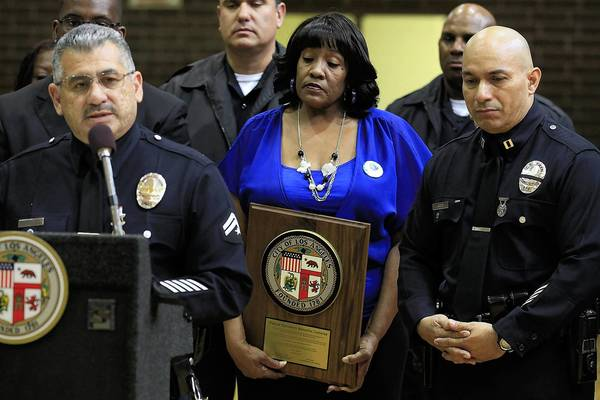 Gail Sears, center, mother of slain park volunteer Patrick Caruthers, holds a plaque honoring her son at a news conference announcing the installation of security cameras at Jackie Tatum Harvard Recreation Center in Los Angeles.