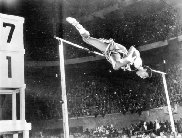 In 1959, while a freshman at Boston University, John Thomas sails over the bar at the Millrose Games in New York, becoming the first person to jump 7 feet indoors.