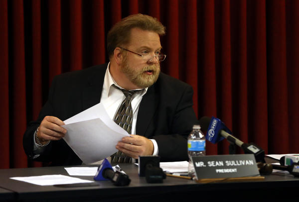 District 207 school board president Sean Sullivan finishes reading a statement detailing the firing of Maine West soccer coach Emilio Rodriguez following a closed door meeting in Park Ridge.
