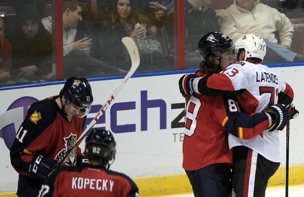 Florida Panthers Peter Mueller and Ottawa Senators Guillaume Latendresse hug it out during the second period.