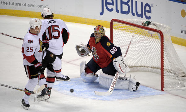 Florida Panthers goalie Jose Theodore tries to keep his eyes on the puck in front of Ottawa Senators Zack Smith and Chris Neil during the first period.