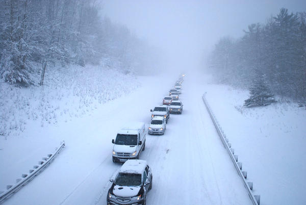 A seemingly endless row of vehicles creeps along I-75 through blustery conditions Monday after a pileup in Crawford County slowed traffic and caused more runoffs in Otsego County.