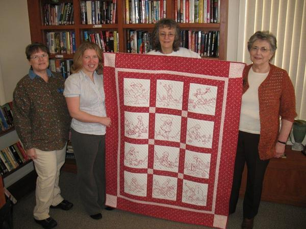Embroidered redwork panels of childhood days are featured in a quilt made by Little Traverse Bay Quilt Guild and donated to the Petoskey Friendship Center for its Valentine's Day fundraising raffle. Accepting on behalf of Friendship Centers of Emmet County is (second from left) Char Delis, marketing and development project director, from quilt guild members (from left) Renee Prevo, Lois Hart and Lois Furness.