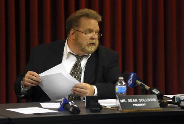 District 207 board President Sean Sullivan reads a statement Thursday on the board's decision to suspend Maine West soccer coach Emilio Rodriguez without pay over allegations of hazing. Rodriguez was coach of the freshman boys team.