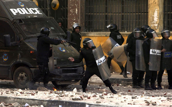 Police throw stones back at protesters during clashes in Alexandria, Egypt. Youths fought Egyptian police in Cairo and Alexandria on the second anniversary of the revolt that toppled Hosni Mubarak and brought the election of an Islamist president.