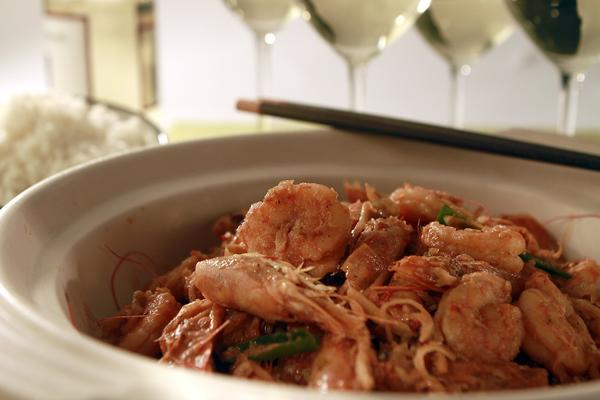 Caramelized lemongrass shrimp served with white rice and white wine.